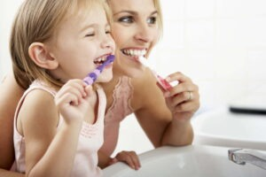 Mother And Daughter Brushing Teeth Together